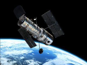 Photo of the Hubble Space Telescope in orbit above Earth